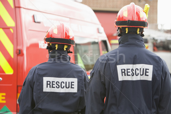 Firefighters standing by a small fire engine Stock photo © monkey_business
