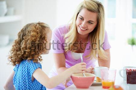 Two young women enjoying a tea party while one sits apart Stock photo © monkey_business