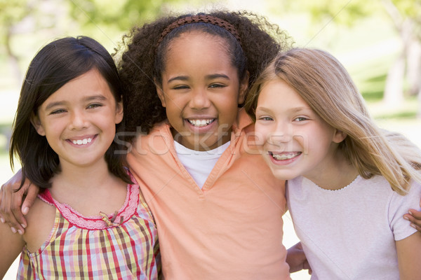 Three young girl friends outdoors smiling Stock photo © monkey_business