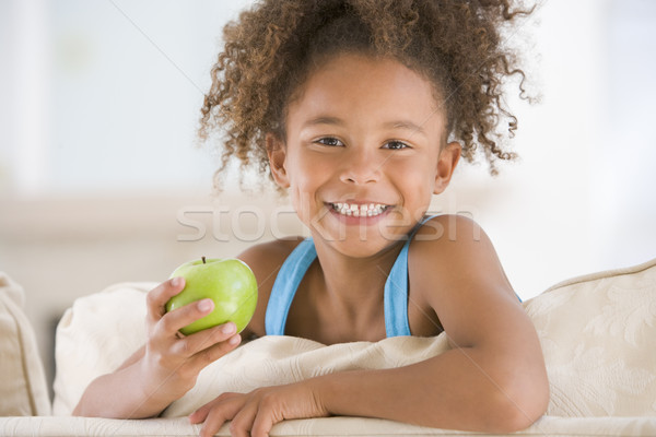 Jeune fille manger pomme salon souriant alimentaire Photo stock © monkey_business