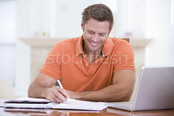 Homem sala de jantar laptop escrita sorridente tabela Foto stock © monkey_business