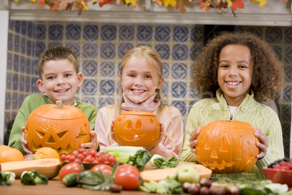 Three young friends on Halloween with jack o lanterns and food s Stock photo © monkey_business