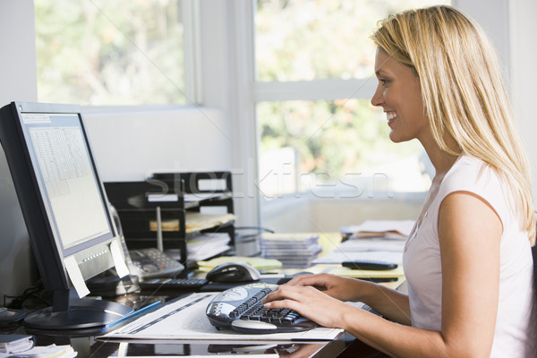 Woman in home office with computer smiling Stock photo © monkey_business