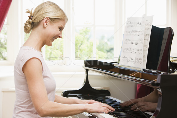 Woman playing piano and smiling Stock photo © monkey_business