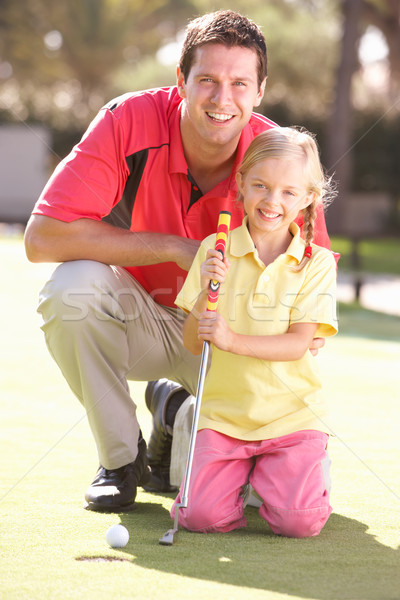 Father Teaching Daughter To Play Golf On Putting On Green Stock photo © monkey_business
