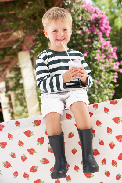 Young Boy Wearing Wellington Boots Drinking Milkshake Stock photo © monkey_business