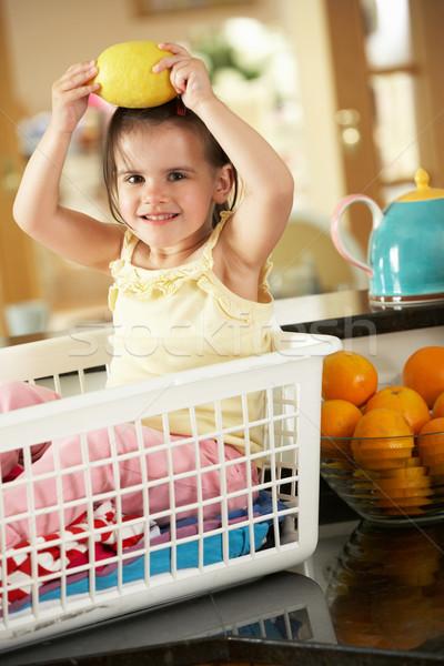 Ragazza seduta cestino di lavanderia contatore di cucina limone bambini Foto d'archivio © monkey_business