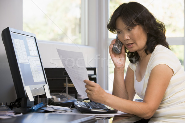 Stock photo: Woman in home office with paperwork using telephone