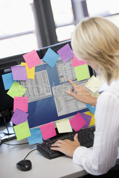 Stock photo: Businesswoman in office pointing at monitor with notes on it