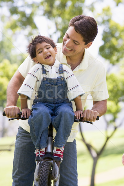 Stock photo: Man and young boy on a bike outdoors smiling