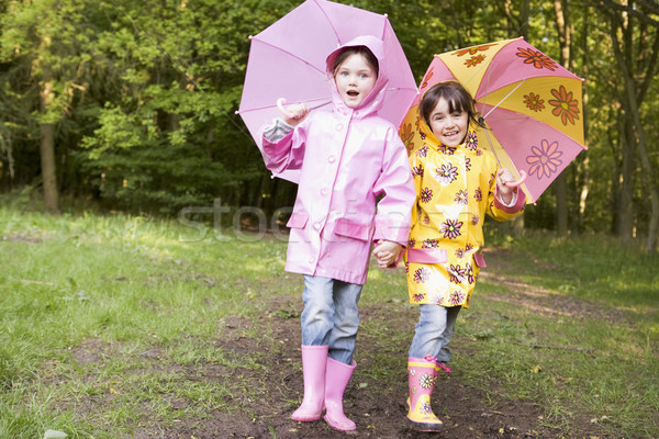 Two sisters outdoors with umbrellas smiling Stock photo © monkey_business