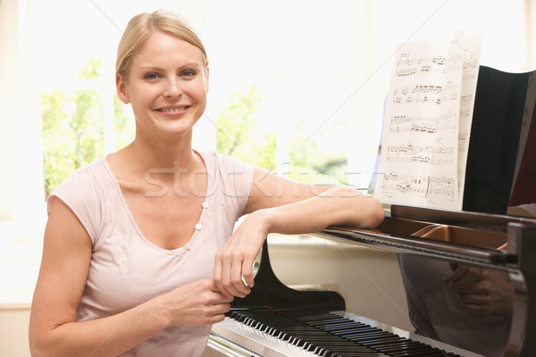 Woman sitting at piano and smiling Stock photo © monkey_business