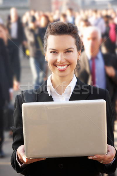 Female commuter in crowd using laptop Stock photo © monkey_business