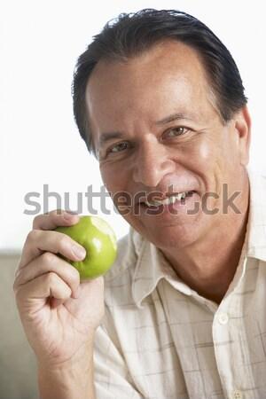 Középkorú férfi eszik zöld alma mosolyog kamera Stock fotó © monkey_business