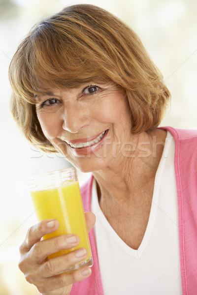 Middle Aged Woman Drinking Fresh Orange Juice Stock photo © monkey_business