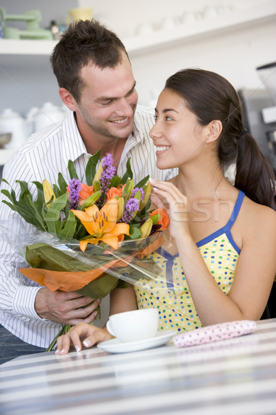 A young man giving flowers to a young woman in a cafe Stock photo © monkey_business