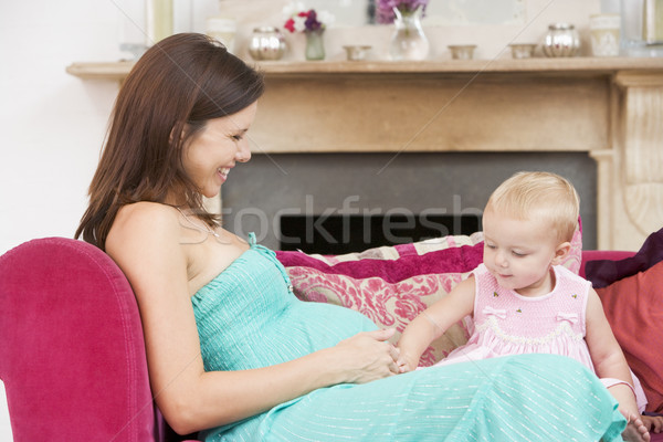 Pregnant mother with daughter in living room touching belly and  Stock photo © monkey_business