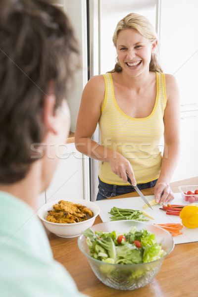 Stock photo: Woman Talking To Husband While Preparing meal,mealtime