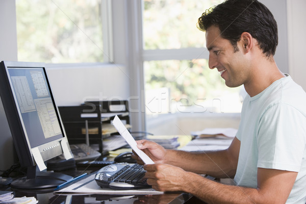 Man in home office using computer holding paperwork and smiling Stock photo © monkey_business