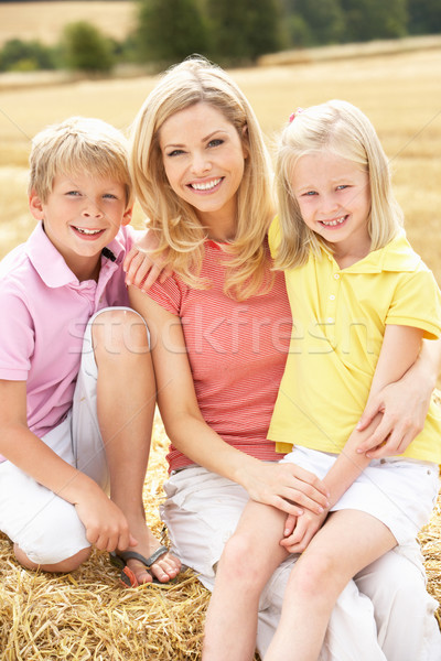 Mother And Children Sitting On Straw Bales In Harvested Field Stock photo © monkey_business