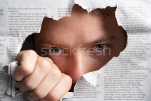 Man looking through hole in newspaper Stock photo © monkey_business