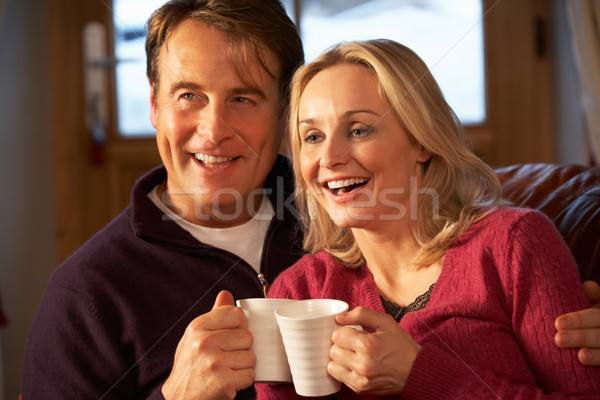 Middle Aged Couple Sitting On Sofa With Hot Drinks Watching TV Stock photo © monkey_business