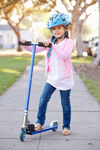 Girl Wearing Safety Helmet Riding Scooter Stock photo © monkey_business