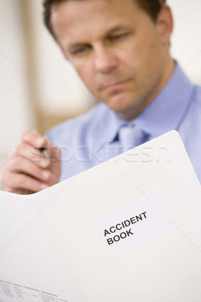 Businessman indoors looking at Accident Book Stock photo © monkey_business