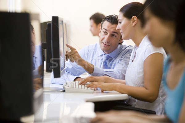 Man assisting woman in computer room Stock photo © monkey_business