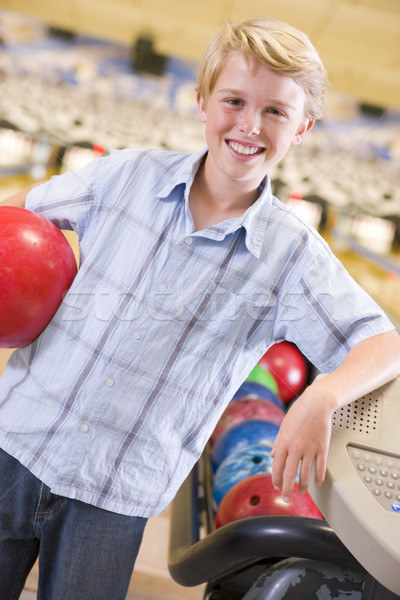 Young boy in bowling alley holding ball and smiling Stock photo © monkey_business