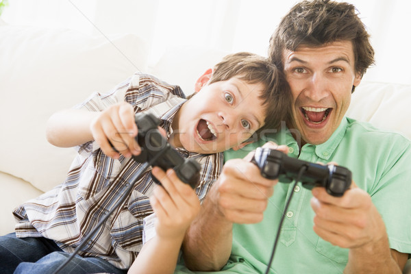 Man and young boy with video game controllers smiling Stock photo © monkey_business