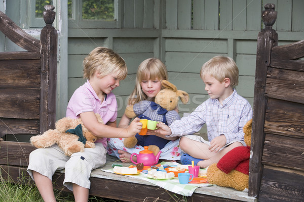 Three young children in shed playing tea and smiling Stock photo © monkey_business