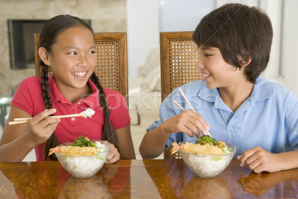 Two young children eating Chinese food in dining room smiling Stock photo © monkey_business