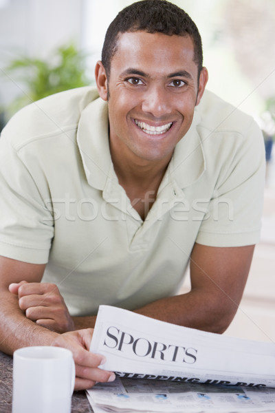 Man in kitchen reading newspaper and smiling Stock photo © monkey_business