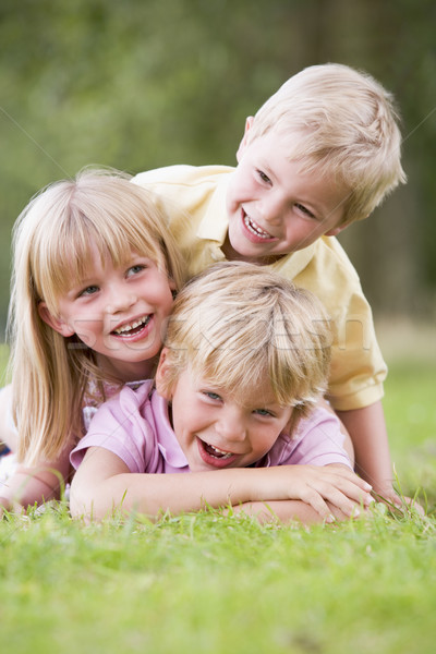 Three young children playing outdoors smiling Stock photo © monkey_business