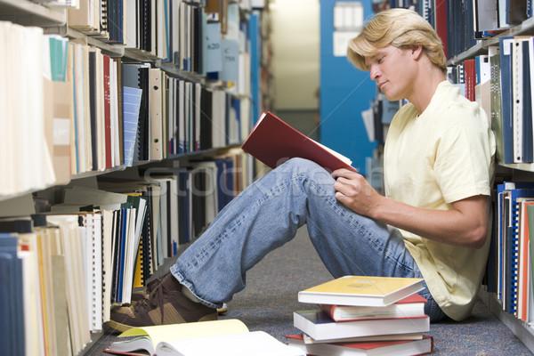 Egyetemi hallgató dolgozik könyvtár férfi ül padló Stock fotó © monkey_business