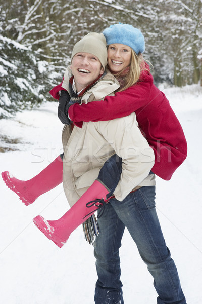 Man Giving Woman Piggyback In Snowy Woodland Stock photo © monkey_business
