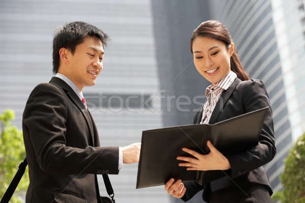 Chinese Businessman And Businesswoman Discussing Document Outsid Stock photo © monkey_business