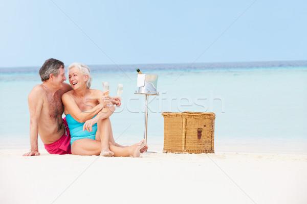 Senior Couple On Beach With Luxury Champagne Picnic Stock photo © monkey_business