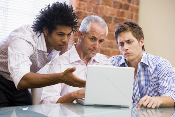 Three businessmen sitting in office with laptop Stock photo © monkey_business