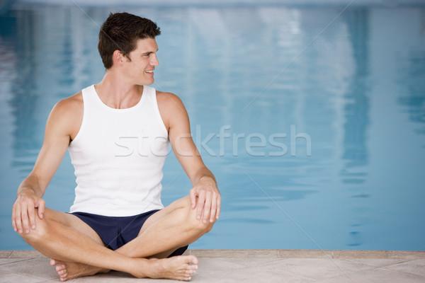 Man sitting poolside smiling Stock photo © monkey_business