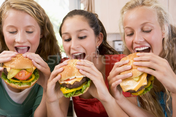 Tinilányok eszik étel otthon konyha lányok Stock fotó © monkey_business