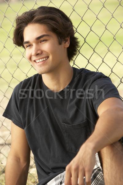 Posiedzenia boisko człowiek szczęśliwy teen Zdjęcia stock © monkey_business