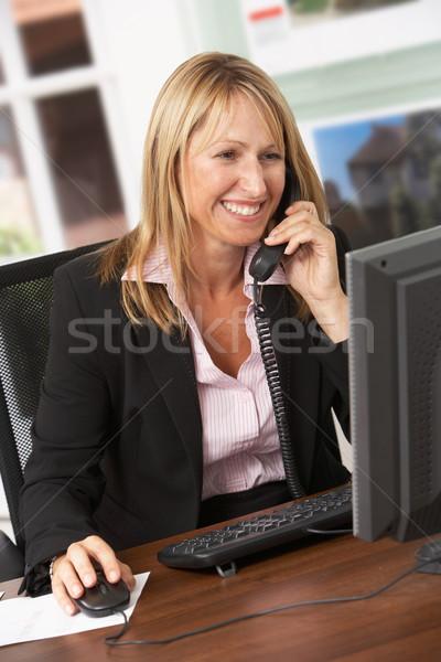 Feminino corretor de imóveis falante telefone secretária trabalhando Foto stock © monkey_business