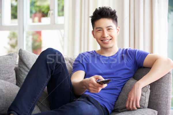 Young Chinese Man Sitting And Watching TV On Sofa At Home Stock photo © monkey_business