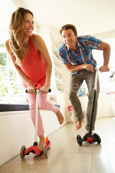 Couple Riding Childrens Scooters Indoors Stock photo © monkey_business