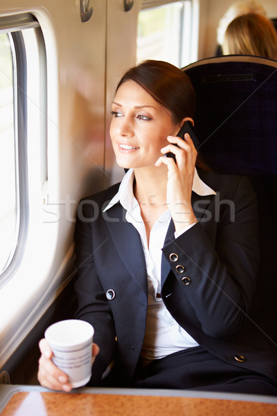 Female Commuter With Coffee On Train Using Mobile Phone Stock photo © monkey_business