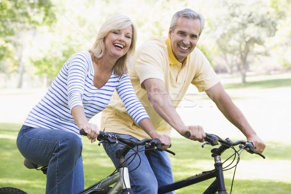 Stock photo: Couple on bikes outdoors smiling