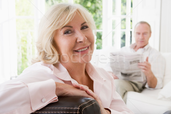 Woman in living room smiling with man in background reading news Stock photo © monkey_business