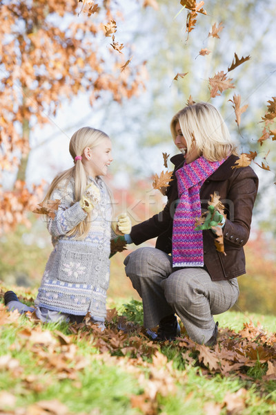 Mother and daughter throwing leaves in the air Stock photo © monkey_business